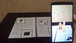 Com o telefone celular, é possível, ao apontar para o desenho no livro, ver as figuras em 3D, no formato realidade aumentada (foto: divulgação)